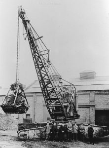 It is shown here, outside the Priestman works in Hull with the two Priestman Brothers amongst those posed alongside it. The track frames appear to be all that is left of the original vehicle but notice the two large containers at the front, probably to hold water and coal and to act as a counterbalance when lifting a load.